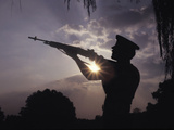 A US Marine Honor Guard Rifleman Performs a Gun Salute During Sunset