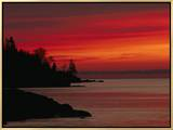 A Bright Red Sky over Lake Superior at Dawn with Silhouettes of the Rocky Coast