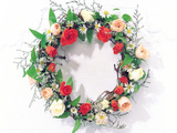 Wreath of Pink  Red And White Roses And Green Vines on White Wall