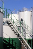 Worker Inspecting An Oil Storage Tank