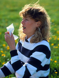Woman Sitting In Meadow Sneezing