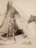 A Native American Stands at the Entrance to His Teepee Holding a Rifle  1880-90