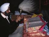 A Sikh Granthi Waving a Chauri over the Guru Granth Sahib in a Temple