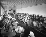 Women Workers in a Factory Warehouse Take a Dinner Break  Supervised by a Few Male Overseers