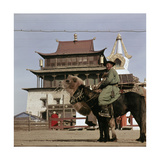 Mongolian on Horseback Transporting His Yurt on a Camel  in the Centre of Ulan Bator