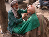 A Street Barber in Kabul Shaving a Man for the Hajj Pilgrimage