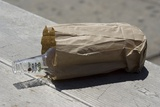Discarded Rum Bottle In Paper Bag