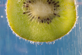 A Slice of Kiwi Fruit in a Glass of Sparkling Mineral Water