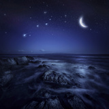 Rising Moon over Ocean and Boulders Against Starry Sky