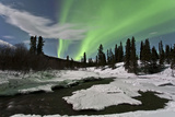 Aurora Borealis over Creek  Yukon  Canada