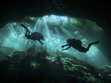 Two Divers Silhouetted in Light at Entrance to Chac Mool Cenote  Mexico