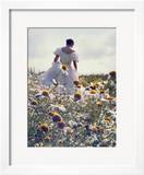A Woman in a White Victorian Dress  Walking Among Camomile Flowers on a Meadow on a Sunny Day