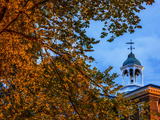The Cupola Atop Bates College Framed by Tree Branches Bearing Autumn-Hued Leaves