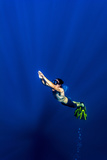 A Free-Diver Ascends Through Sun Rays from the Deep Ocean Depths