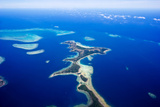 A Sand Spit Island Surrounded by Coral Reefs and a Vast Blue Ocean