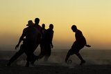Silhouetted Men Playing Soccer at Sunset