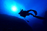 A Scuba Diver Exhales Bubble Rings as He Floats Towards the Surface