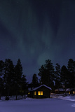 The Northern Lights or Aurora Borealis over Warmly-Lit Cottages and Silhouetted Evergreen Trees