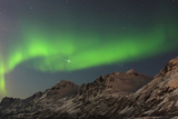 The Northern Lights  or Aurora Borealis  Dance over Rugged Mountains