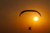 Silhouette of a Microlight and Passenger in Flight at Sunset