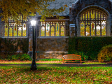 A Bench Outside a Row of Colorful Stained Glass Windows  in the Bright Light of a Streetlamp