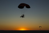 Silhouettes of Two Microlights and Passengers in Flight at Sunset