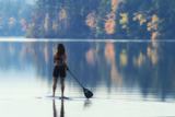 A Paddle Boarder Paddling on a Still Lake in Autumn