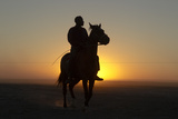 A Silhouetted Man on Horseback at Sunset