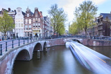 Long Exposure of a Tourist Boat Crossing Canals Keizersgracht from Leidsegracht at Dusk