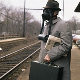 1960s-1970s Man Commuter Waiting for Train Wearing Gas Mask Pollution