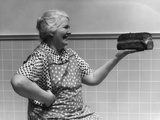 1930s-1940s Grandmother in Apron Admiring Loaf of Freshly Baked Bread