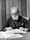 1930s Elder Man in Glasses Sitting at Desk Reading Book