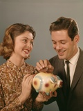 1950s-1960s Happy Couple Man Woman Putting Coins into Savings Piggy Bank