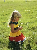1980s Little Blond Girl Wearing Red and Yellow Sun Dress Kneeling on Grass