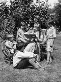 1920s Older Woman Sitting in Wicker Chair Reading Book to Grandchildren