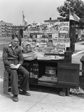 1940s Boy Sitting at Corner Newsstand Writing in Notepad