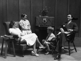 1930s Family of Four in Living Room Gathered around Listening to Radio