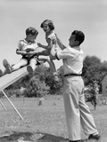 1950s Father Lifting Son and Daughter onto a Playground Seesaw Outdoor
