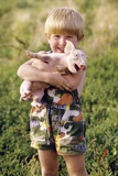Smiling Blond 4 Year Old Boy Holding Squealing Baby Pig