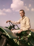 1960s Portrait Man Farmer Sitting on Green Tractor Smoking Cigarette