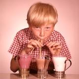 1950s-1960s Boy Drinking Three Milkshakes Through a Straw at Same Time