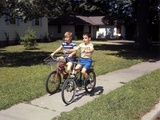 1970s Two Boys Riding Bikes Down Suburban Neighborhood Sidewalk
