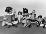 1930s Girl Pointng a Finger Reading to a Row of Dolls Toys Stuffed Animals