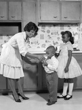 1960s Woman in Apron and Pumps Giving a Glass of Milk to Son and Daughter