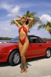 1980s Woman in Red Swimsuit in Front of Red Sports Car