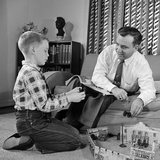 1950s Father and Son Playing with Cowboy Toy Game in Living Room Indoor