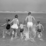 1960s Back View of Family of 5 Holding Hands Running into Ocean