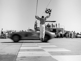 1960s Man Jumping Waving Checkered Flag as Winning Sports Car Crossing the Finish Line
