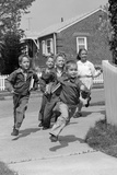 1950s School Children Running around Corner of Picket Fence in Suburban Neighborhood
