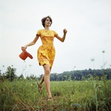 1970s Young Woman Wearing Colorful Print Dress Running in Field Carrying Red Straw Hat